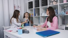Mãe e filha nova ao doutor O doutor fêmea usa um estetoscópio para examinar a menina bonito no hospital Em video estoque