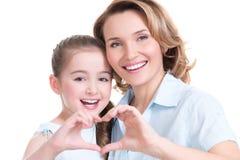 A mãe e a filha nova com coração dão forma ao sinal Fotos de Stock