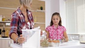 Mãe e filha nova junto na cozinha vídeos de arquivo