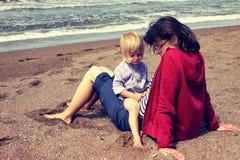 Mãe e filha nova que sentam-se na praia fotos de stock