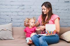 Mãe e filha novas de dois anos de branco louro velho do portátil do laptop do uso com a cópia brilhante que senta-se no sofá dent foto de stock
