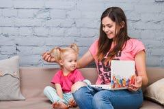 Mãe e filha novas de dois anos de branco louro velho do portátil do laptop do uso com a cópia brilhante que senta-se no sofá dent Fotografia de Stock