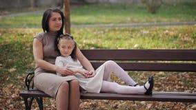 A mãe e a filha novas estão descansando em um parque da cidade em um banco Uma família feliz filme