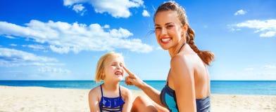 Mãe e filha novas felizes na praia que aplica o bloco do sol foto de stock