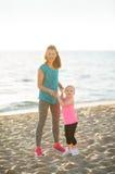 Mãe e filha novas felizes na praia que guarda as mãos Foto de Stock Royalty Free