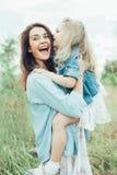 A mãe e a filha novas na grama verde foto de stock