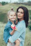 A mãe e a filha novas na grama verde imagens de stock