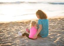 A mãe e a filha novas no exercício alinham o assento na praia Fotos de Stock