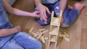 Mãe e filha para construir uma torre de blocos de madeira video estoque