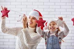 A mãe e a filha penduram uma festão Fotografia de Stock