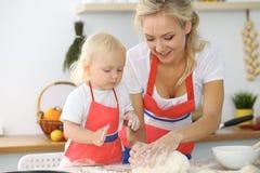 A mãe e a filha pequena estão cozinhando na cozinha Passando o tempo todo junto ou conceito de família feliz Imagem de Stock Royalty Free
