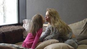 A mãe e a filha pequena estão sentando-se na cama e em estalar video estoque