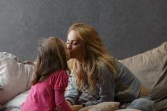 A mãe e a filha pequena estão sentando-se na cama e em estalar foto de stock