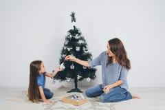 Mãe e filha pequena que decoram a árvore de Natal fotos de stock royalty free