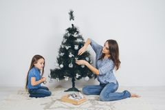 Mãe e filha pequena que decoram a árvore de Natal imagem de stock royalty free