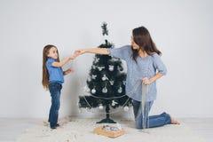 Mãe e filha pequena que decoram a árvore de Natal foto de stock royalty free
