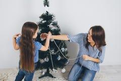 Mãe e filha pequena que decoram a árvore de Natal Imagem de Stock