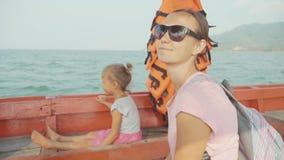 Mãe e filha pequena que flutuam no barco de motor no movimento lento vídeos de arquivo