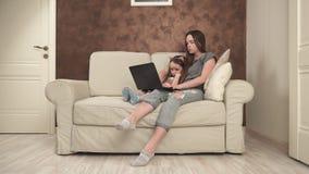 Mãe e filha pequena que usa o portátil video estoque