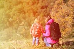 A mãe e a filha pequena viajam em montanhas do outono Imagem de Stock