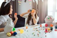 A mãe e a filha preparam-se para a Páscoa Ovos coloridos da posse da menina nos olhos dianteiros A mãe faz o mesmos Têm o diverti foto de stock royalty free