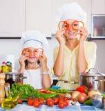 A mãe e a filha preparam vegetais Fotografia de Stock Royalty Free