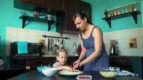 A mãe e a filha puseram o salame sobre a base da pizza vídeos de arquivo