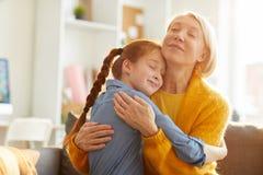 Mãe e filha que abraçam maciamente imagem de stock