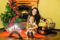 Mãe e filha que abraçam presentes imagem de stock