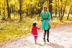 A mãe e a filha que andam no outono estacionam, vista traseira imagens de stock royalty free