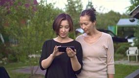 Mãe e filha que andam e que olham fotos no smartphone filme
