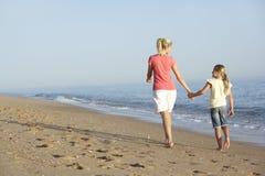 Mãe e filha que apreciam a caminhada ao longo da praia Imagem de Stock