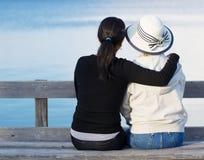 Mãe e filha que apreciam seu tempo no lago Foto de Stock