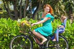 A mãe e a filha que bicycling ao longo do mar lixam a praia Imagens de Stock Royalty Free