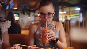 Mãe e filha que comem com rolos de madeira dos hashis Menina adolescente que bebe o suco de cenoura fresco de um vidro video estoque
