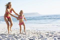 Mãe e filha que correm ao longo da praia que veste junto o traje de natação imagem de stock