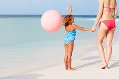 Mãe e filha que correm na praia bonita com balão Imagens de Stock Royalty Free