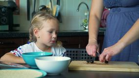 Mãe e filha que cortam azeitonas na cozinha video estoque