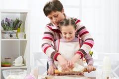 Mãe e filha que cozinham em casa, fazendo a massa para bolos Fotos de Stock Royalty Free