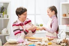 Mãe e filha que cozinham em casa, fazendo a massa para bolos Foto de Stock Royalty Free