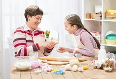 Mãe e filha que cozinham em casa, fazendo a massa para bolos Imagens de Stock