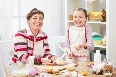 Mãe e filha que cozinham em casa, fazendo a massa para bolos Fotos de Stock
