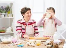 Mãe e filha que cozinham em casa, fazendo a massa para bolos Imagem de Stock