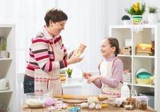 Mãe e filha que cozinham em casa, fazendo a massa para bolos Foto de Stock