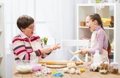 Mãe e filha que cozinham em casa, fazendo a massa para bolos Imagens de Stock Royalty Free