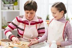 Mãe e filha que cozinham em casa, fazendo a massa para bolos Imagem de Stock Royalty Free