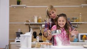 Mãe e filha que cozinham junto na cozinha vídeos de arquivo