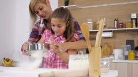 Mãe e filha que cozinham junto na cozinha video estoque