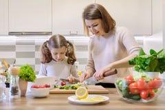 A m?e e a filha que cozinham junto na salada, no pai e na crian?a vegetais da cozinha est?o falando o sorriso imagem de stock royalty free