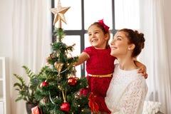 Mãe e filha que decoram a árvore de Natal imagem de stock royalty free
